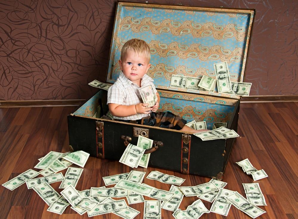 bambino piccolo seduto in una valigia piena di soldi