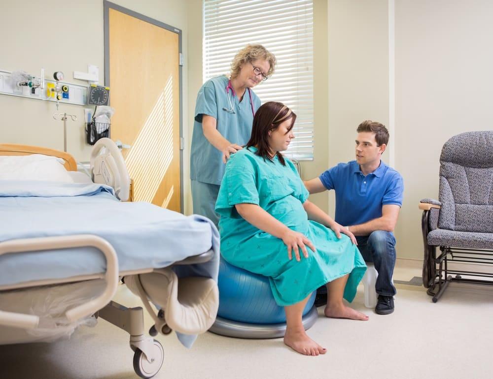 donna in procinto di partorire assistita da uomo e ostetrica