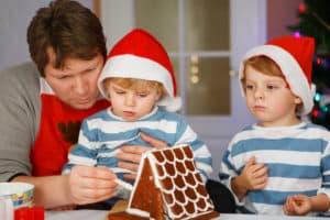 padre e figli preparano casetta di pan di zenzero per Natale